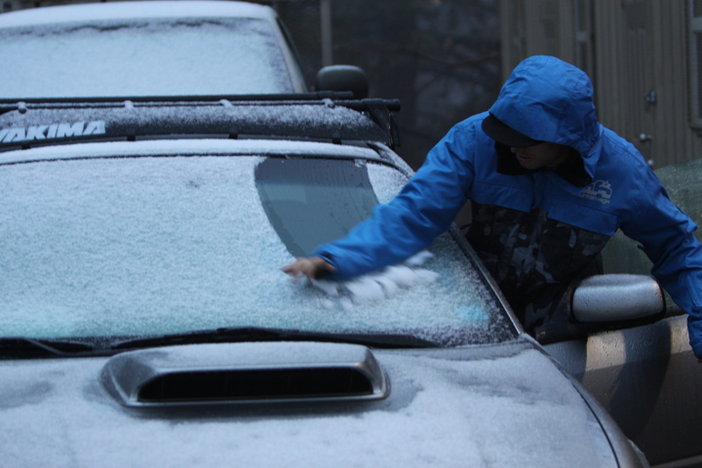 Early morning groomer wiping the snow off his windsheild.