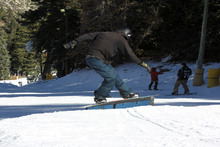 Skate-style frontside boardsilde on the skate-style rail.
