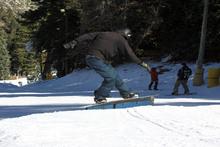 Skate-style frontside boardsilde on the skate-style rail.